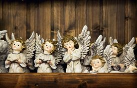 stock photo of christmas angel  - Christmas angels toy with the sparked wings on a wooden wall background - JPG