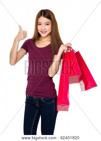 Young woman hold with shopping bag and thumb up