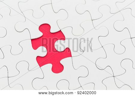 Jigsaw puzzle with missing piece over red background