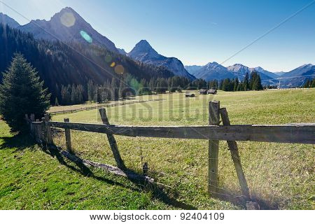 Beautiful sunny landscape of village with old wooden fence at foot of mountain range
