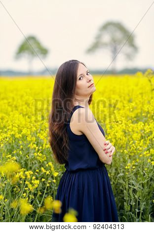 Profile of young beautiful woman with dark blue sleeveless dress and long dark hair standing on yellow blooming rapeseed field with crossed arms