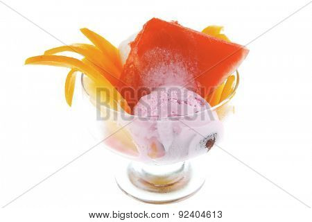 small transparent glass cup with ice cream and tropical fruits isolated on white background