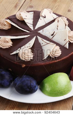 chocolate cream brownie cake topped with white chocolate slice and cream flowers decorated with fruits apple plum and grape on plate on wooden table