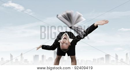 Businesswoman bent over and evading from book
