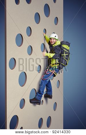 smiley man in equipment holding on climbing wall and showing thumbs up over blue background