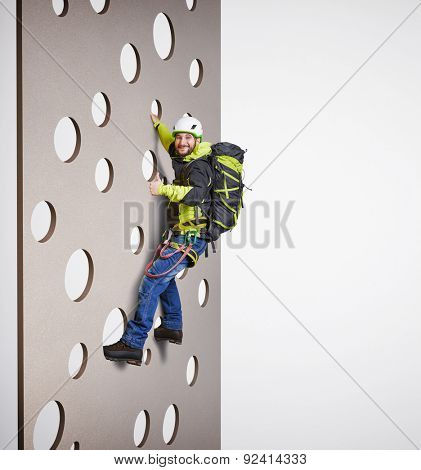 smiley man in equipment holding on climbing wall and showing thumbs up over white background