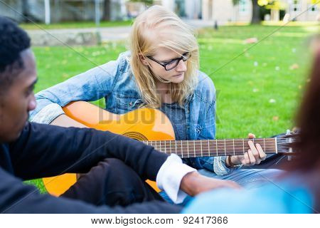 Group of young people in park making music singing song and playing guitar