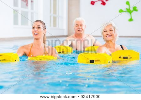 Senior and young people in water gymnastics with resistance device