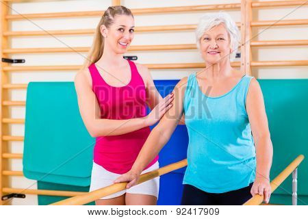 Walking Rehab in with senior woman, trainer guiding her to remobilization
