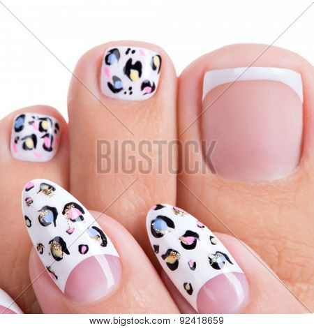 Beautiful woman's nails of hands and legs with beautiful french manicure, pedicure with art design