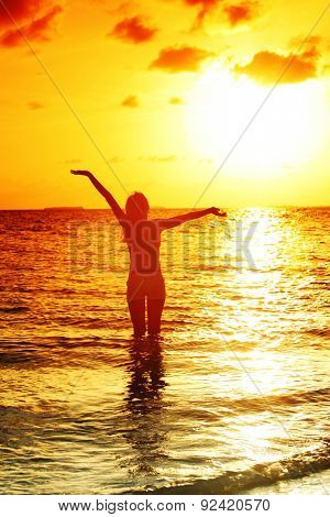 happy woman standing on a sunset in ocean waves