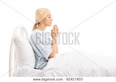 Young female patient lying in a hospital bed and praying to god isolated on white background