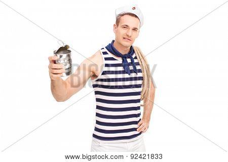 Young male sailor crushing a can with bare hands and looking at the camera isolated on white background