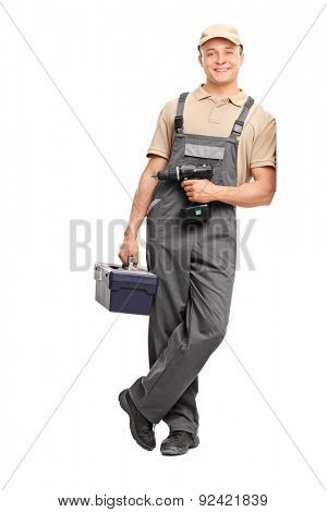 Full length portrait of a young worker in gray uniform holding a toolbox and a hand drill and leaning against a wall isolated on white background
