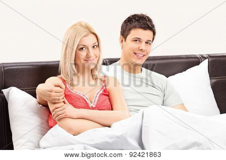 Young couple lying in bed and posing together covered with blanket in a bedroom