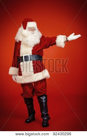 Full length portrait of Santa Claus showing something. Christmas time. Red background.
