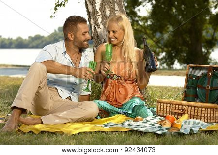 Young happy caucasian casual couple drinking champagne sitting at picnic. Handsome man and attractive woman smiling, romance, outdoor.