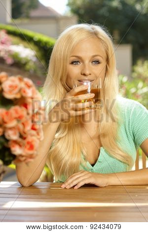 Portrait of attractive young blonde busty caucasian woman sitting and drinking at table, outdoors, in a summer garden with flowers. Smiling.