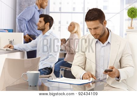 Businessman looking at diagrams, holding mobilephone, working in busy office.