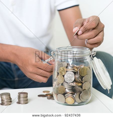 Savings concept. Focus on hand. Indian guy save money to glass jar.