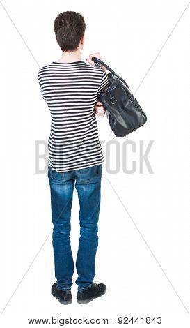 Back view man in jeans with bag. Standing young guy. Rear view people collection.  backside view person. guy in striped shirt with hands on hips standing. guy is throwing his bag on his right shoulder
