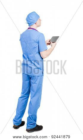 Back view of doctor in robe holding tablet computer. Standing young guy. Rear view people collection.   Isolated over white background.  Physician Assistant compares the data to the computer.