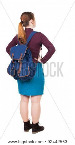Back view woman with backpack looking up. Standing young girl. Rear view people collection.  Isolated over white background. girl with big blue backpack standing with hands on hips.