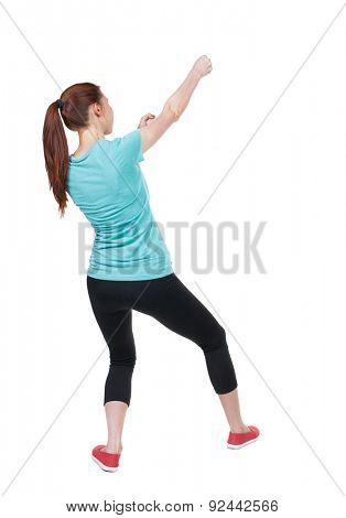 back view of woman in sportswear pulling a rope from the top or cling to something.   Isolated over white background. Sportswoman in tights pulls the top rope.