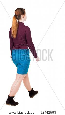 side view of walking  woman in dress. beautiful girl in motion.  backside view of person.  Rear view people collection. Isolated over white background. girl in a skirt and a red jacket goes to right.