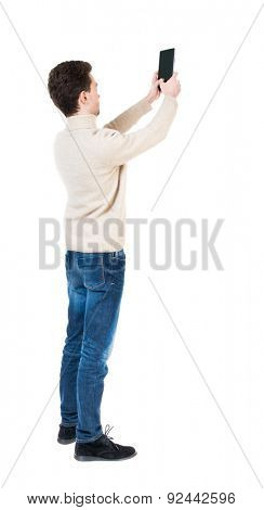Back view of man with tablet. Standing young guy. Rear view people collection.  backside view person.  Isolated over white background. Curly boy in a white warm sweater tablet takes something in sky