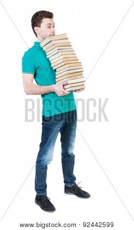 Back view of going  handsome man carries a stack of books. walking young guy . Rear view people collection.  High school student standing with his chin a stack of books.