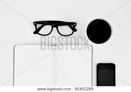 high-angle shot of a blank notebook, a pair of black plastic-rimmed eyeglasses, a cup of coffee and a smartphone on a white table