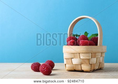 Basket Of Raspberries Against Blue Background