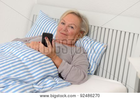 Adult Blond Woman On Her Bed Holding Her Mobile Phone