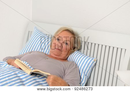 Adult Woman With Book Lying On Bed