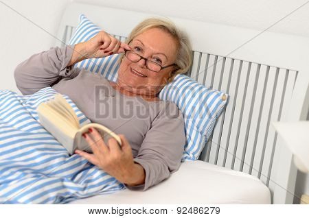 Happy Adult Woman With Book Lying On Bed