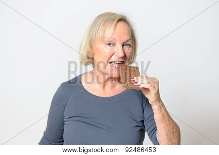 Adult Blond Woman Eating Chocolate Bar In Close Up