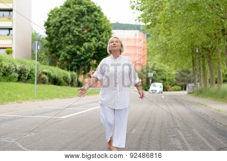 Senior Woman In All White Walking At The Street