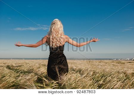 The girl in a black dress standing in the grain field arms sprea