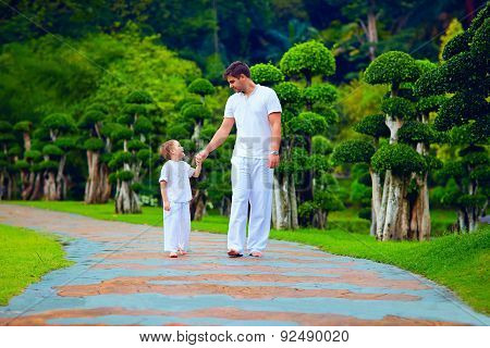 Father Sharing Knowledge With Son, While Walking In Garden