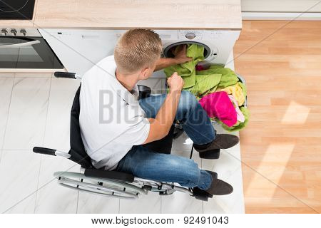Man On Wheelchair Putting Laundry Into The Washing Machine