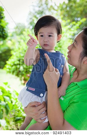 Young Asian Woman And Cute Daughter Talking Together In The Backyard