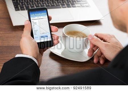 Businessman Looking At Job Application Form On Cellphone