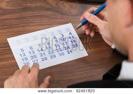 Businessman Holding Pen Looking At Calendar