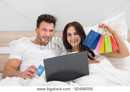 Colorful Shopping Bags With Couple Lying On Bed