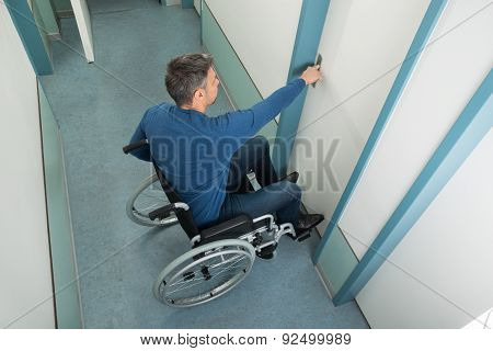 Man Sitting On Wheelchair Opening Door