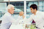 foto of wrestling  - Two businessmen competeting arm wrestling in office - JPG