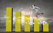 image of step-up  - Young businesswoman stepping up on chart bar - JPG