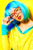 stock photo of wig  - Bright glamorous girl in vivid clothes and a wig alluring over yellow background - JPG