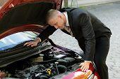 stock photo of breakdown  - Young Man Looking Under The Hood Of Breakdown Car - JPG